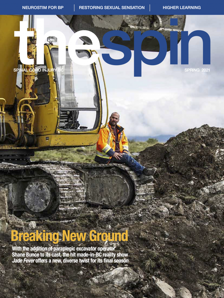Cover photo of The Spin Spring 2021 issue featuring a man sitting on the wheel tracks of a construction digger in Northern BC
