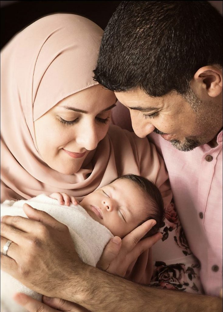 a woman in a hijab and her husband hold their new baby daughter