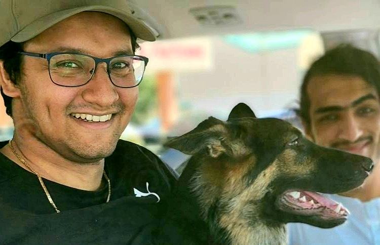 a young man wearing a baseball cap sits in his car with a happy dog beside him and his friend in the background