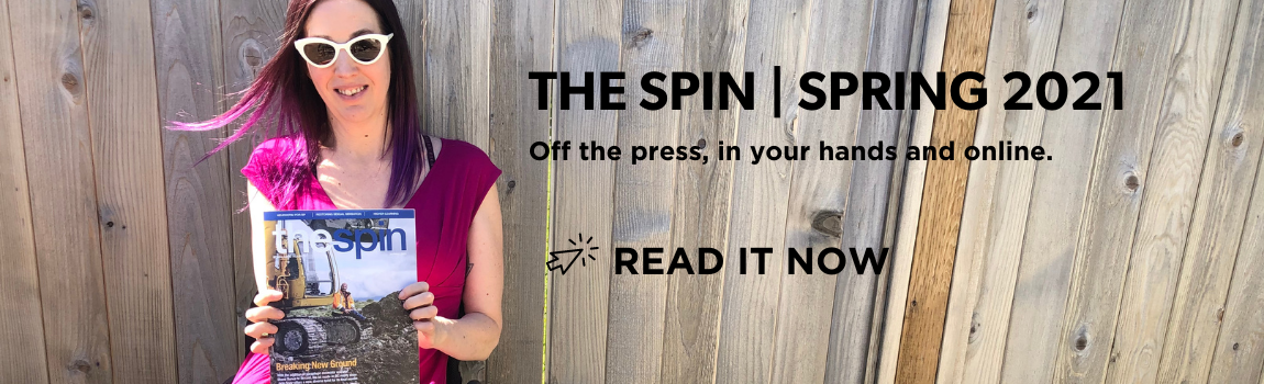 a woman holds the spring 2021 issue of The Spin magazine wearing sunglasses and smiling in the sun