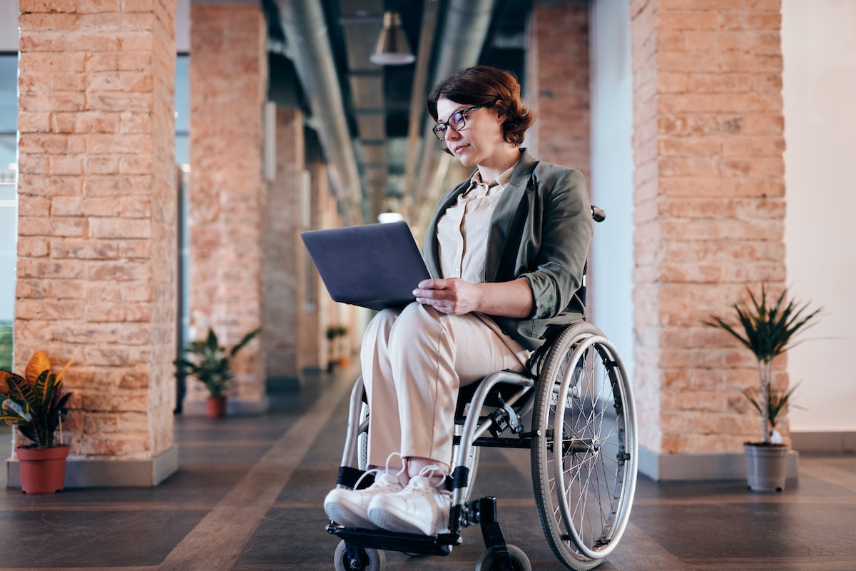 woman in wheelchair consulting her computer