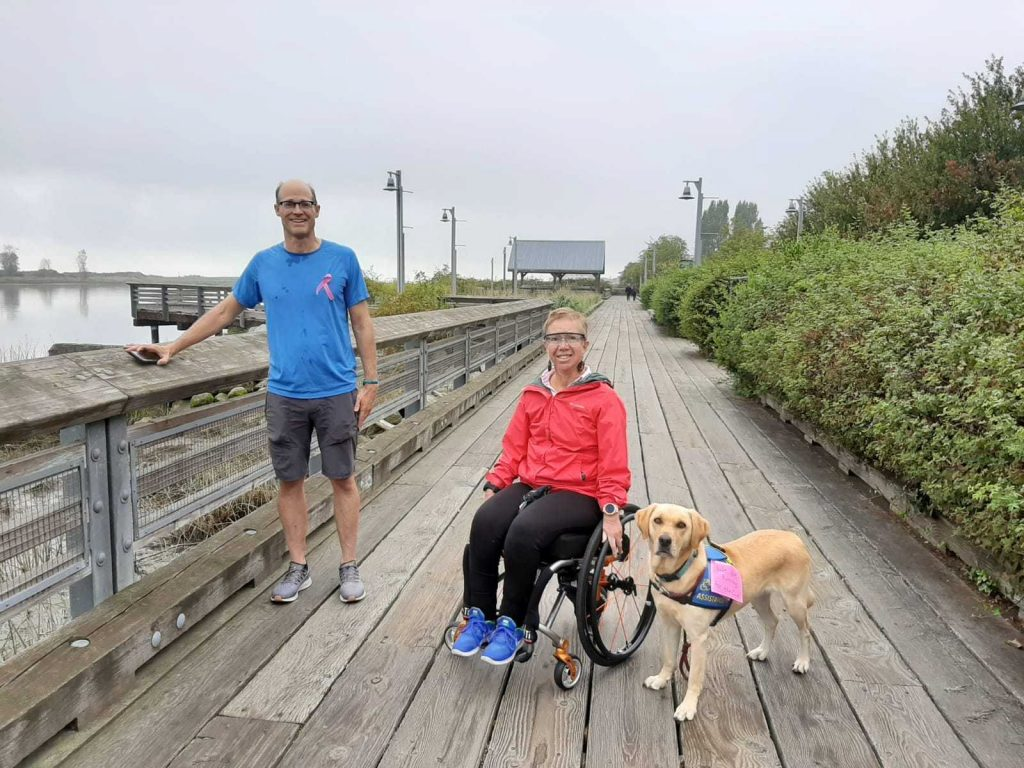 an able-bodied man and a woman in a wheelchair stand together on a boardwalk with a golden labrador retriever. They are training for the Scotiabank Charity Challenge run