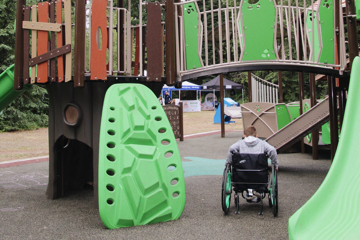 a kid in a wheelchair explores a new accessible playground in Northern BC. He wheels under a bridge on a smooth, flat ground.