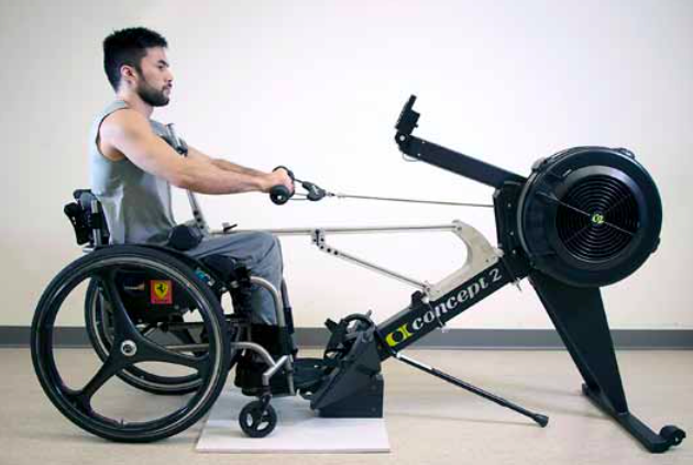 SCI BC peer Leo Sammarelli demonstrates the aROW. His wheelchair is in the locked the position and he rows on an apadted rowing machine at the gym.