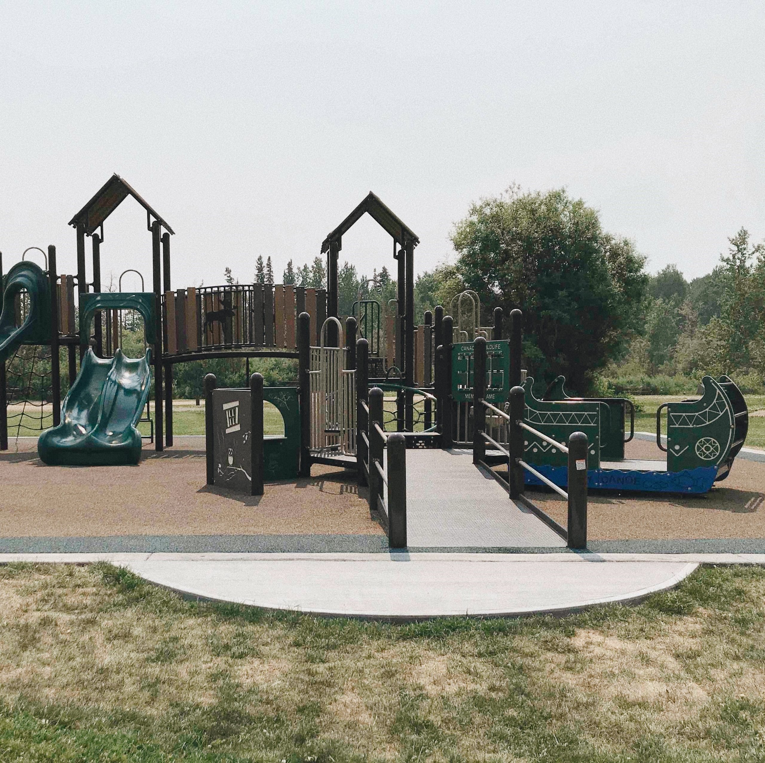 a photo of Swan Lake accessible playground. The playground has a ramp for access and flat ground