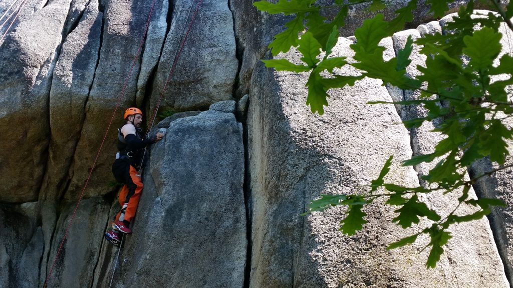 Kevin Priebe wearing modified chaps to protect legs while climbing massive rock wall with a variety of climbing routes