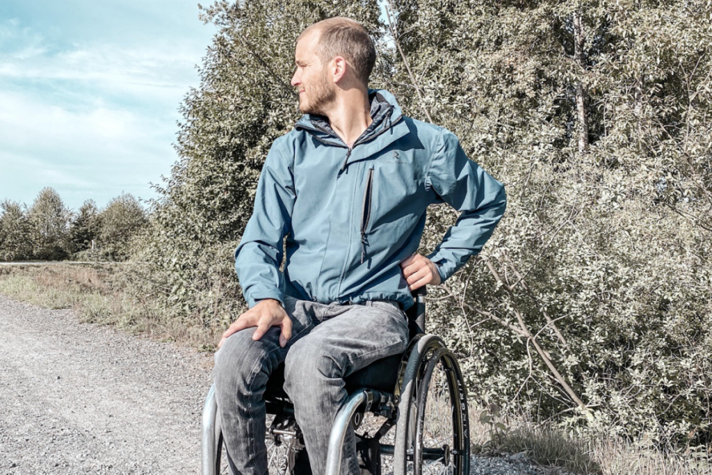 Derek Jezewsky wearing blue technical jacket and black jeans. He's in his wheelchair on a gravel pathway looking over his right shoulder