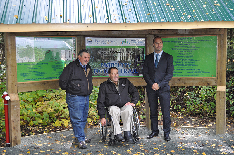 SCI BC Resource Center Manager Pat Harris joins Randy Ellenchuk, vice-president of Tabor Mountain Recreation Society (left) and Scott Dedels, regional sales director of Great West Life (right), at the trailhead of the Great West Life Mobility Trail on Sept. 19, 2014.